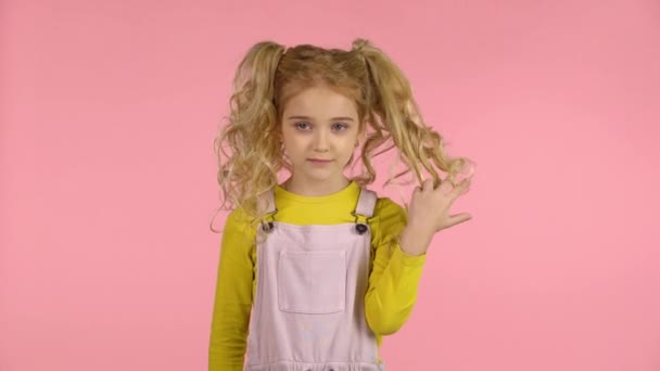 Cute female child is winding her hair on the finger