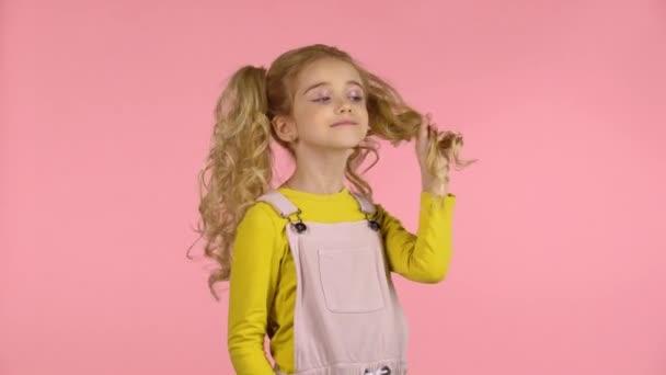 Szép édes kislány játszik a haját