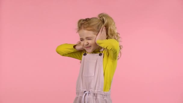 kleines süßes Mädchen bedeckt ihre Ohren im Studio