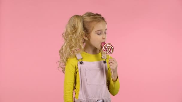 Beautiful girl with a lollipop in studio on pink background