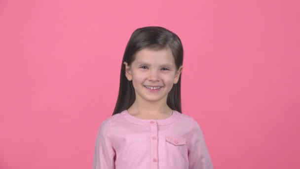 Brunette gyermek mosolyogva a rózsaszín háttér. Lassított mozgás