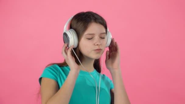 Lány hallgat zenét és táncok nagy fehér fejhallgató rózsaszín háttér. Lassított mozgás