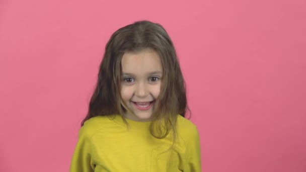 Cute baby screaming with smile on pink background in the studio. Slow motion