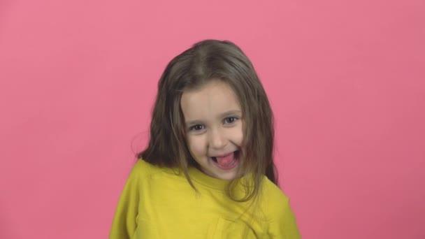 niedlichen Mädchen spielen und machen lustige Gesicht, zeigen Zunge aus auf rosa Hintergrund. Zeitlupe