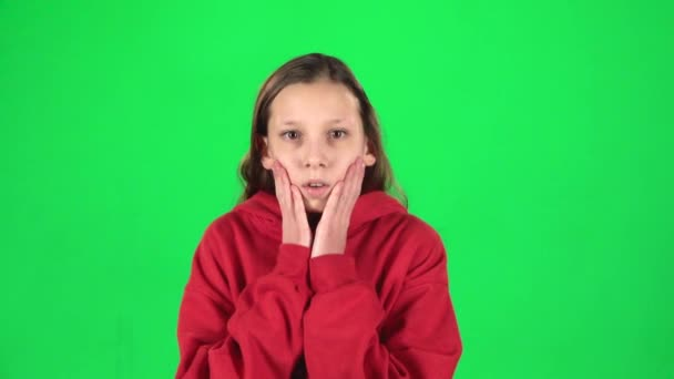 Little female is scared and hiding her face in studio on green background. Slow motion