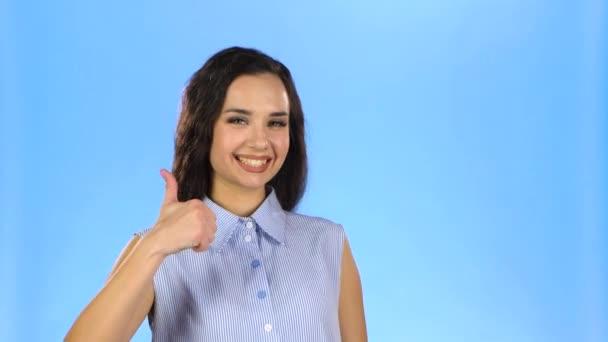 Hezká mladá dáma se usmívá a ukazuje palce nahoru
