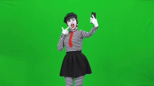 Mime girl making selfie, then choosing good photo. Chroma key.