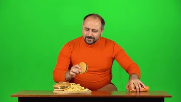 Kaukázusi férfi az asztalnál választ egy tál gyorskaja és egészséges ételek, megáll az egészségtelen ételek, zöld képernyő