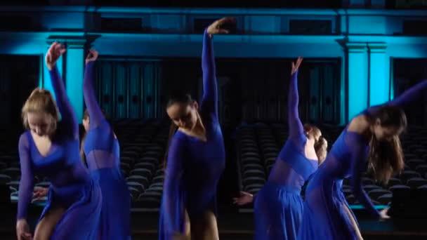 Gruppe junger geschickter Ballerinen, die modernes Ballett auf der Bühne des großen Saals tanzen. Mädchen im Zuschauerraum. Generalprobe vor Auftritt.