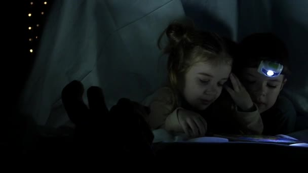 A gyerekek érdekes könyveket olvasnak a takaró alatt. Lassú mozgás.