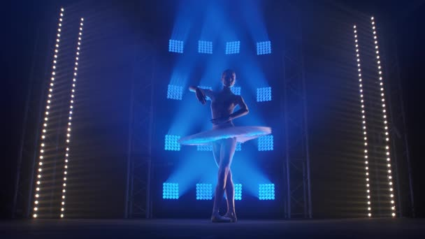 Creative female choreographer setting a ballet performance, dancing and doing various moves in the rays of blue light - arts concept 4k Slow motion footage.