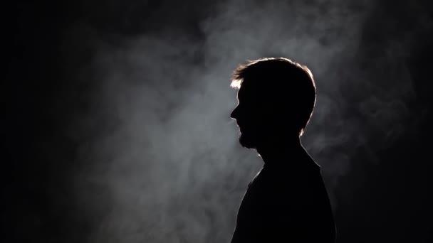 Profilansicht Silhouette bärtiger Mann bläst dicken Rauch beim Rauchen von Wasserpfeife auf schwarzem Hintergrund in Zeitlupe, Nahaufnahme