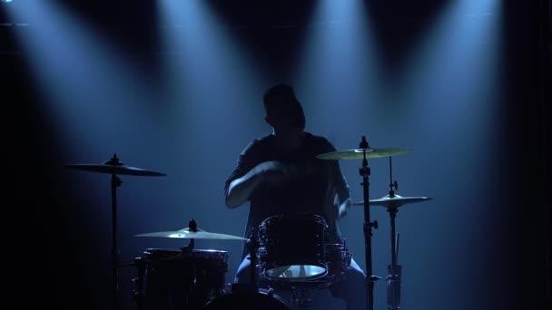 Silhouette-Schlagzeuger spielt auf einem Schlagzeug auf der Bühne in einem dunklen Studio mit Rauch und Neonlicht. Performance Vokal- und Musikband. Nahaufnahme.