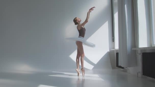 Junge Ballerina im Bühnenkleid mit offenem Rücken probt im Studio am Fenster stehend das Training. Flexibles Mädchen auf weißem Hintergrund in hellem Licht. Zeitlupe.
