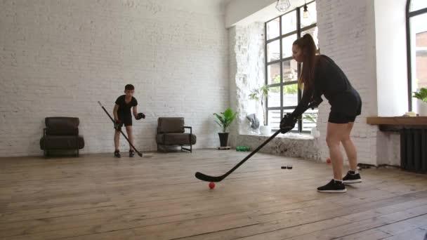 A kis hokijátékos az edzőjével edz egy bottal és egy piros labdával. Lassú mozgás..