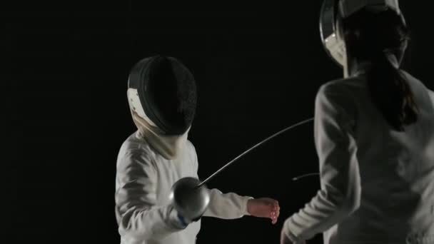 Rückansicht Junge Fechterin in Maske und weißem Anzug tritt im Duell mit einem unbekannten männlichen Fechter an. Schuss isoliert auf schwarzem Hintergrund. Zeitlupe. Nahaufnahme.