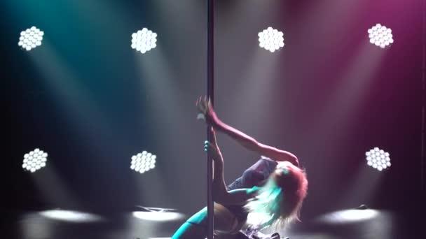 Sexy blondýnka tančí na pylonu a točí se na něm ve spodním prádle a vysokých podpatcích. Erotický tanec. Natočeno v tmavém studiu s kouřem a neonovým osvětlením. Jasné neonové světelné efekty. Silueta. Zavřít.