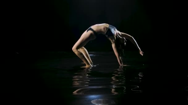 Slender woman in wet sports underwear practicing bridge exercise on the surface of the water. The sexy body is glisten in the studio light. Dark studio. Black background. Slow motion.