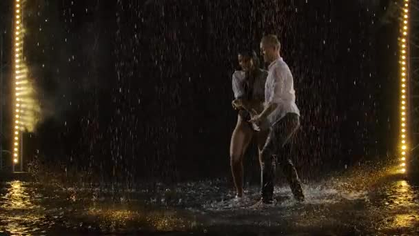Skillful dancers dance salsa in a dark room under the concert lights and smoke. The sensual couple performs an artistic and emotional dance among the raindrops and many splashes. Slow motion.