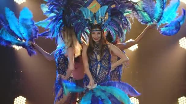 Egy csapat elbűvölő fiatal nő kék brazil karneváli jelmezben, kalapban és tollrajongóban táncol a stúdióban. Tánc női show a háttérben a dinamikus neon fények lassított felvételen. Közelről..