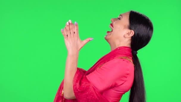 Das Porträt einer jungen Inderin im nationalen klassischen roten Sari blickt geradeaus mit einem sehr glücklichen und freudigen Wow-Gesichtsausdruck. Seitenansicht. Grüner Bildschirm.