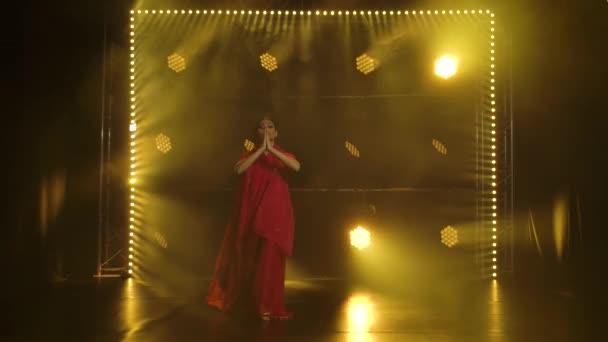 Mladá tanečnice v červeném sárí. Indický lidový tanec. Natočeno v tmavém studiu s kouřem a žlutým neonovým osvětlením. Zpomalený pohyb.