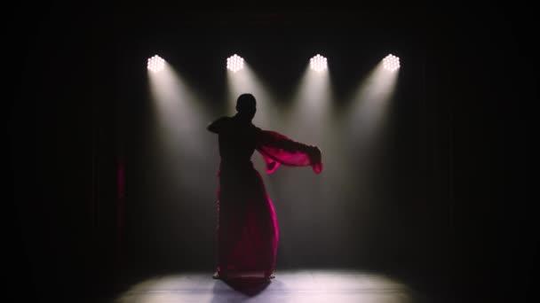 Silueta mladé tanečnice v červeném sárí. Indický lidový tanec. Natočeno v tmavém studiu s kouřem a neonovým osvětlením. Zpomalený pohyb.