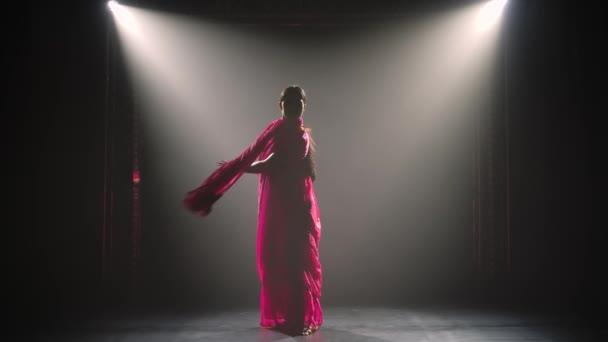 Silueta mladé tanečnice v červeném sárí. Indický lidový tanec. Natočeno v tmavém studiu s kouřem a neonovým osvětlením.Zpomalený pohyb.