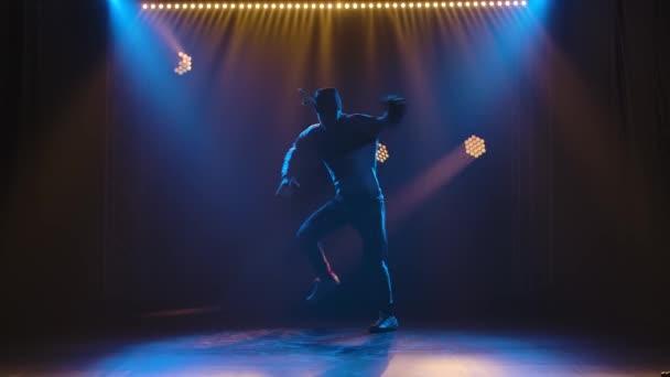 Professionelle Darbietung von Breakdance, Hip Hop, dargeboten von einem stilvollen männlichen Streetdancer. Silhouette eines Mannes im Trainingsanzug und Turnschuhen vor dem Hintergrund inszenierten Lichts. Zeitlupe.