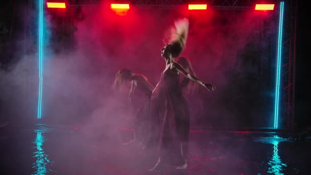 Contemporary choreography performed by a group of young women. Females dance on a smoky background with raindrops. Slow motion.