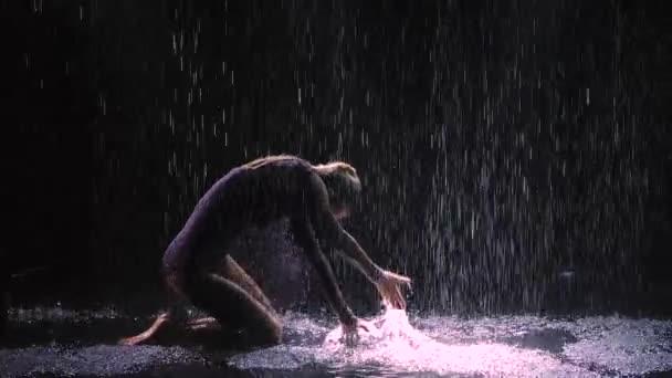 Fekete háttér mellett az esőben, egy fiatal pár táncos szenvedélyesen táncol. Jive egy sötét füstös stúdióban. Lassú mozgás. Közelről..
