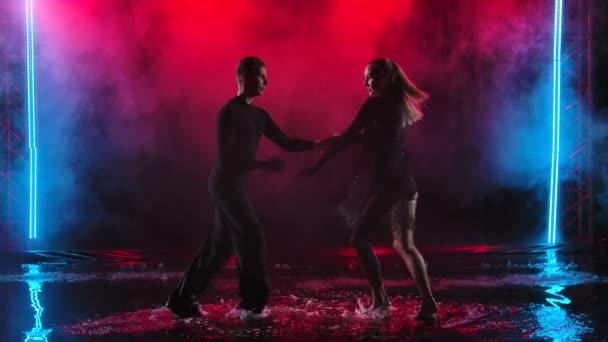 Lächelndes glückliches Tanzpaar, das im dunkel verrauchten Studio mit farbigen Lichtern Jive einübt. Tanzen auf der Wasseroberfläche mit vielen Spritzern. Zeitlupe.