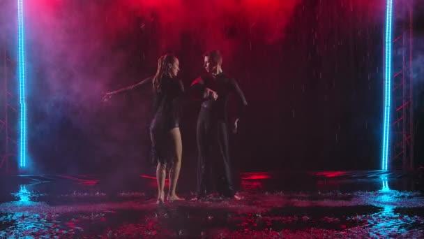 Jive-Elemente, vorgetragen von einem leidenschaftlichen Paar im Regen. Fotografiert in einem dunklen Studio vor einem rauchigen Hintergrund mit farbiger Beleuchtung. Zeitlupe.