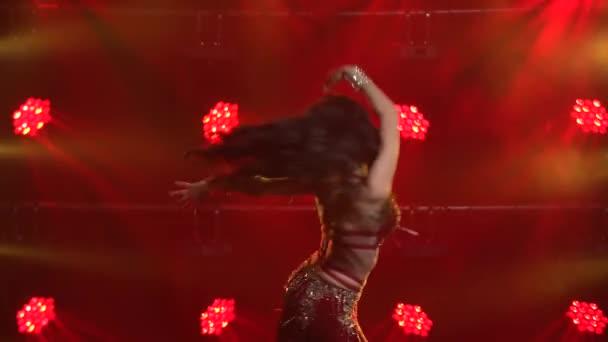 Junge Bauchtänzerin führt klassische Bewegungen des orientalischen Tanzes auf. Sanfte Handbewegungen. Gedreht in einem dunklen Studio mit Rauch und rotem Neonlicht. Nahaufnahme.