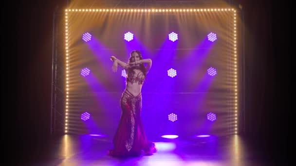 Verführerische traditionelle orientalische Bauchtänzerin, die auf Rauch und blauem Neonlicht tanzt.