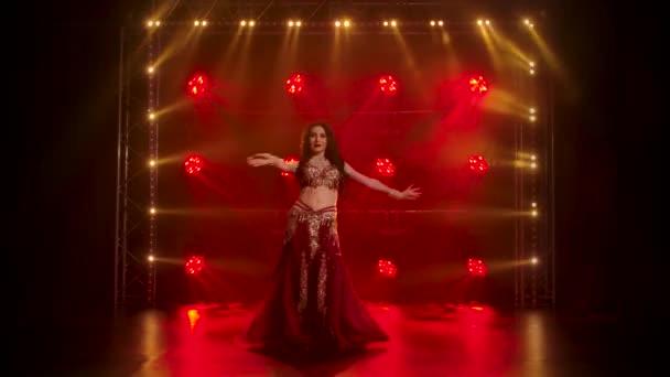 Mädchen im glänzenden orientalischen Kostüm führen klassischen Bauchtanz auf. Gedreht in einem dunklen Studio mit Rauch und roter Neonbeleuchtung.