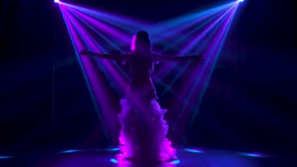 Bauchtänzerin im weißen orientalischen Kostüm schüttelt die Hüften. Gedreht in einem dunklen Studio mit Rauch und Neonlicht. Silhouetten eines schlanken, flexiblen Körpers.