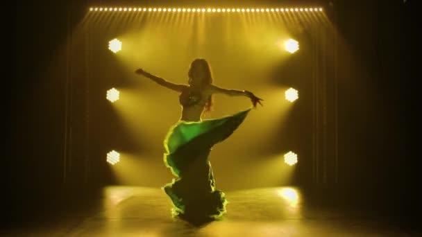 Silhouette Mädchen in einem grün glänzenden orientalischen Kostüm führt klassischen Bauchtanz auf. Gedreht in einem dunklen Studio mit Rauch und gelbem Neonlicht.