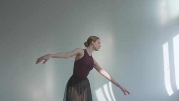 Die Ballerina führt geschmeidige Bewegungen mit den Händen aus und tanzt in Spitzenschuhen auf den Zehenspitzen in der Probe. Auftritt in einem Studio, das in Sonnenlicht getaucht ist. Aus nächster Nähe. Zeitlupe.