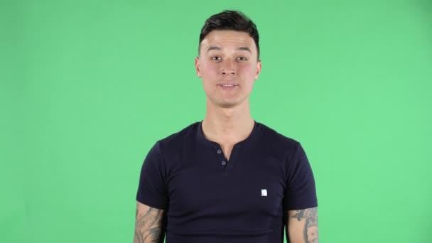 Porträt eines gutaussehenden jungen Mannes blickt in die Kamera und zeigt zwei Finger Siegesgeste. Grüner Bildschirm.