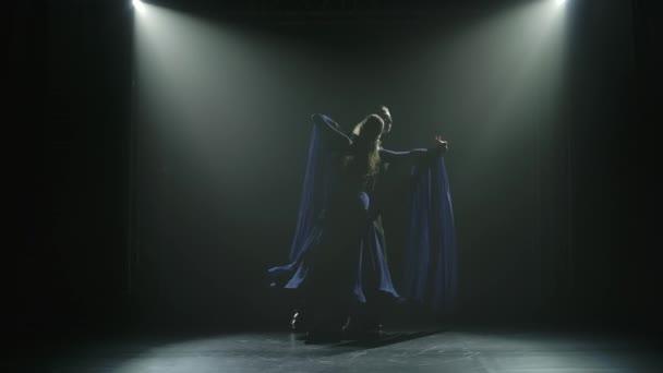 Silhouetten eines tanzenden Paares, das in einem dunklen, verrauchten Studio mit Gegenlicht einen Walzer übt. Zeitlupe.