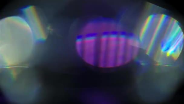 A nap fénylik a mennyei környezetben. A fénysugarak a lassan forgó gyémánton fekete háttér mellett haladnak át, és kék és lila árnyalatokban ragyogó csúcsfényeket hoznak létre. Lassú mozgás. Közel.