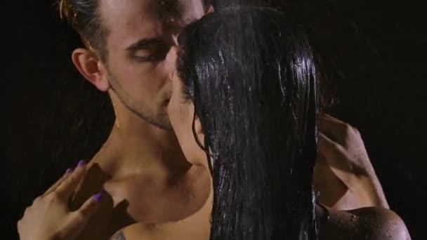 Nackte Paare mit schönen nassen Körpern genießen einander, während sie in der Dusche stehen. Wassertropfen in Großaufnahme tropfen aus dem schwarzen Haar einer Frau und ihrem Körper in Zeitlupe.