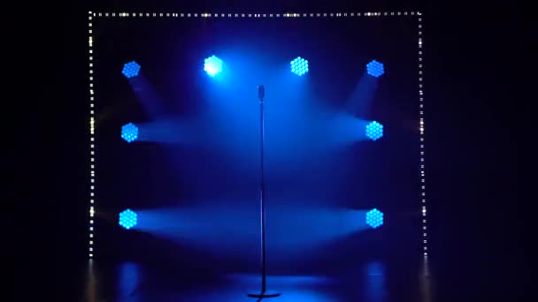 The studio has a retro style microphone set against dynamic blue neon spotlights and smoke. Vintage silver microphone for sound, music, karaoke. Live pop, rock music.