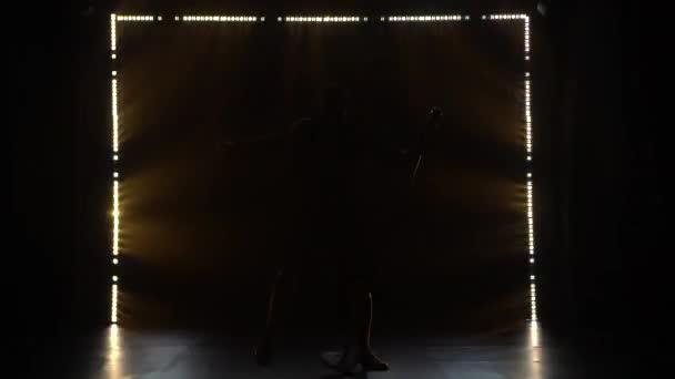 Rockové představení mužského frontmana zpěváka v tmavém ateliéru s pestrobarevnými světly. Silueta muže, který se chová excentricky a potřásá hlavou.