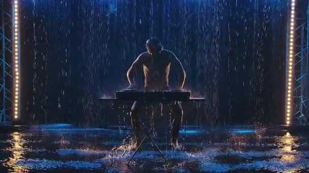 Vonzó férfi DJ táncol és zenél egy sötét stúdióban, kék fénnyel. Egy meztelen, esőcseppekben csillogó férfi sziluettje. Lassú mozgás..