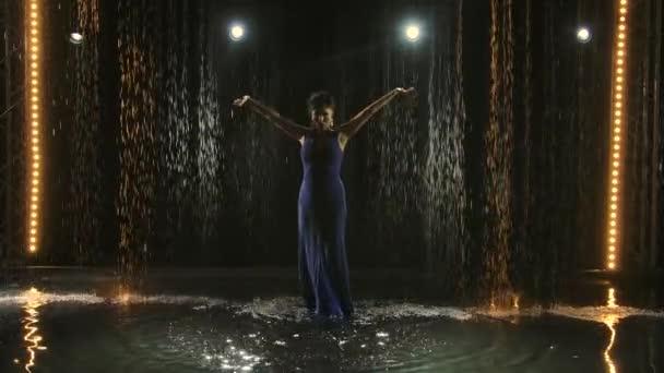 Ein leidenschaftlicher Tänzer des hetzerischen Tanzes des argentinischen Flamenco. Eine Frau tanzt im Studio zwischen Regentropfen und Wasserspritzern. Licht von hinten. Zeitlupe.