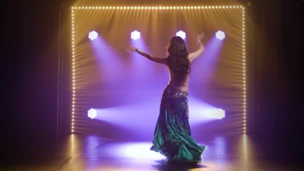 Arabische Bauchtänzerin im exotischen Tanz. Gedreht in einem dunklen Studio mit Rauch und Neonlicht. Zeitlupe.