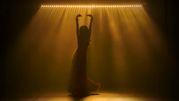 Silhouetten einer Frau in exotischem Kostüm führen einen Bauchtanz auf, der halbnackte Körper bewegt. Gedreht in einem dunklen Studio mit Rauch und gelbem Neonlicht. Zeitlupe.