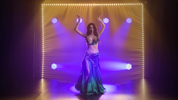 Frau in exotischem Kostüm führt einen Bauchtanz auf halbnacktem Körper auf. Gedreht in einem dunklen Studio mit Rauch und grünem Neonlicht. Zeitlupe.